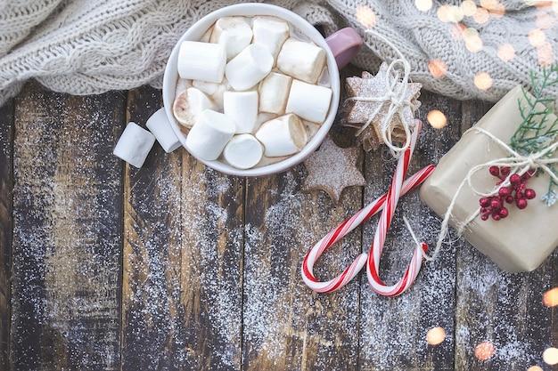 マシュマロ、キャンディー、クリスマスライトと茶色の木製テーブルの上のクッキーとカプチーノの大きなカップ。