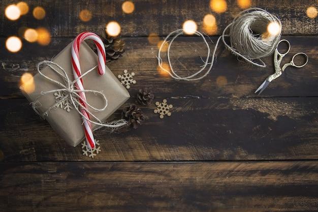 茶色の木製テーブルの上のキャンディー杖とペーパークラフトに包まれたクリスマスプレゼント。
