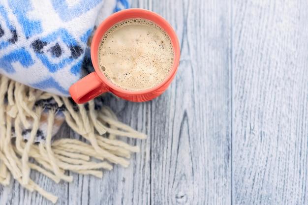 一杯のコーヒーと木製のテーブルに青の模様の暖かい毛布。