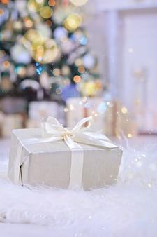 クリスマスツリーの下の白いリボンとクリスマスプレゼント。