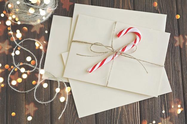 クリスマスライトと茶色の木製テーブルの上の手紙とクリスマスの装飾。