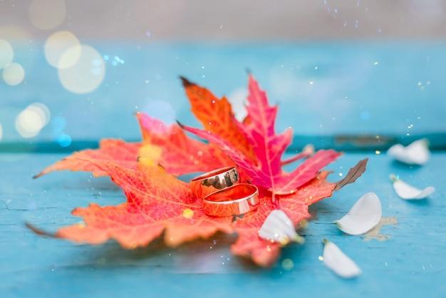 ターコイズブルーの木製テーブルにオレンジ色の紅葉の結婚指輪