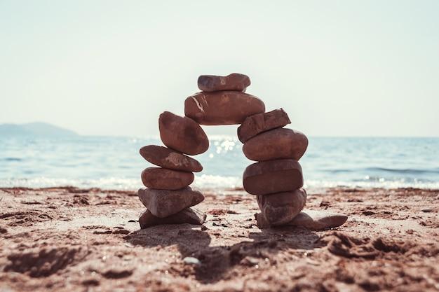 海の夏のビーチに石のアーチ