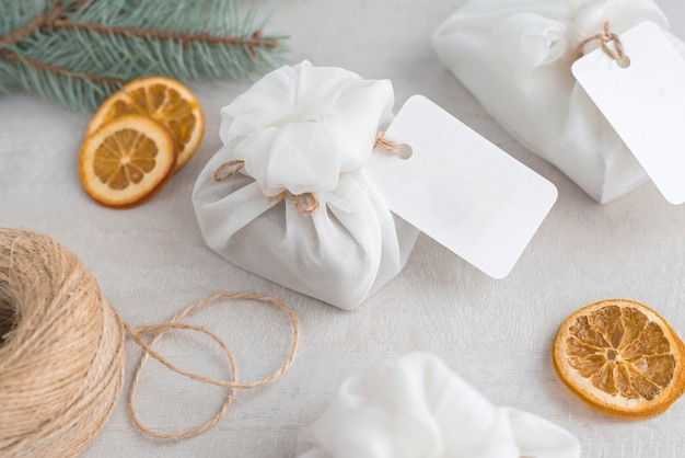 Рождественские подарки, завернутые в белую ткань фурошики, этикетки и сушеные апельсиновые дольки. экологичный подарок.