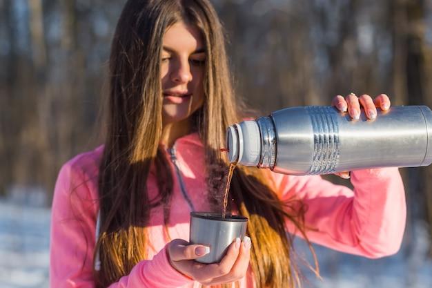 美しい若い女性はお茶を注ぐ