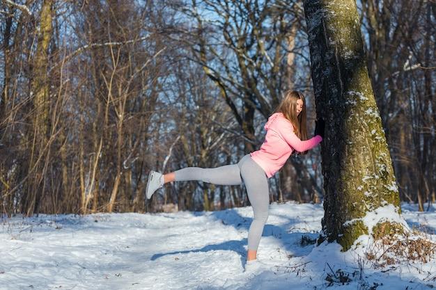 冬の公園で若い女の子がスポーツに行きます。