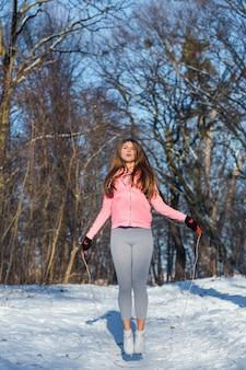 Активная молодая женщина выполняет упражнение со скакалкой