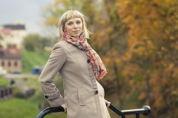 太陽フレアの葉で光のトレンチコートを着て秋のファッションの女の子