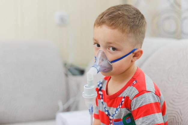 Кавказский мальчик вдыхает пары, содержащие лекарства, чтобы остановить кашель.