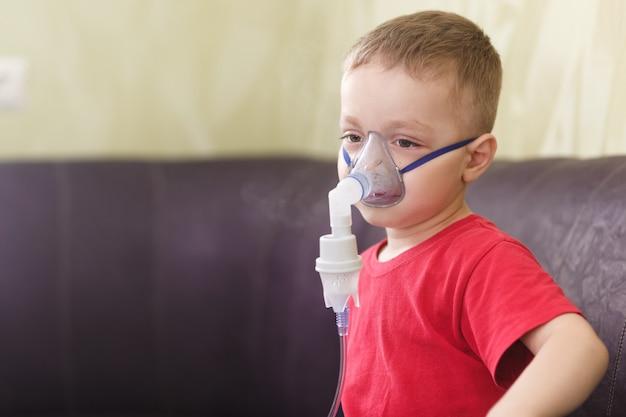 小さな男の子は治療用吸入をします