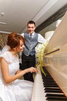 結婚式のカップルがピアノで遊んで