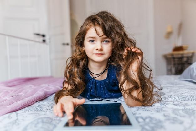 デジタルタブレットを使用して巻き毛を持つかわいい女の子