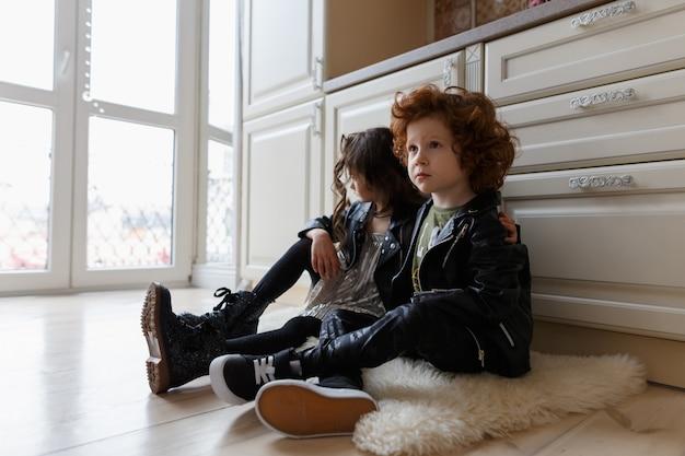 男の子と女の子の友達が一緒に床に座る