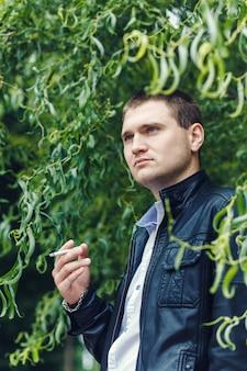クローズアップハンサムな若い男の喫煙タバコ
