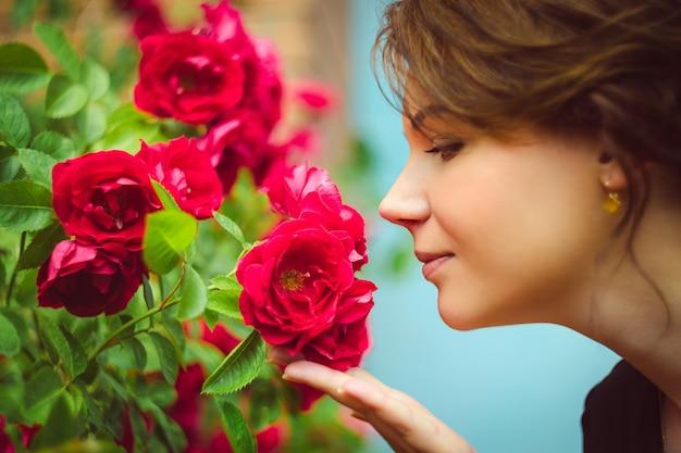 Красивая женщина пахнущие красные розы