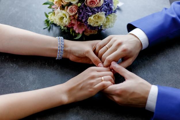 リングでの結婚式の手のクローズアップ