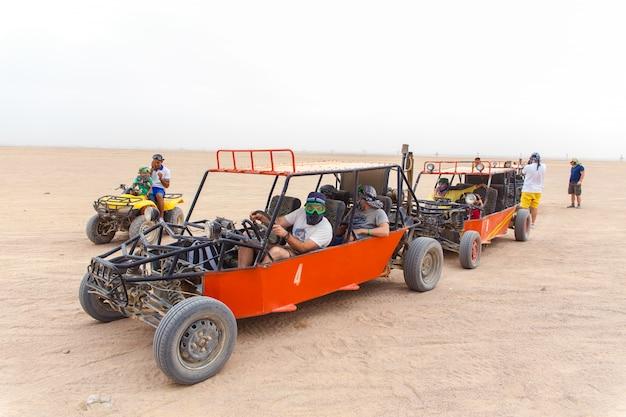 砂漠でレースをする準備ができている観光客
