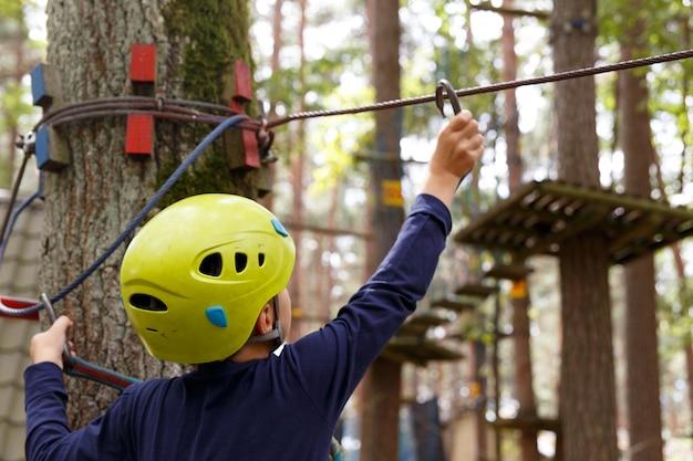 ヘルメットの少年は、冒険の遊び場で彼の余暇を過ごします。