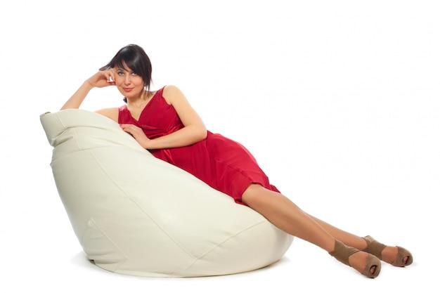 Женщина в красном платье сидит на кресле