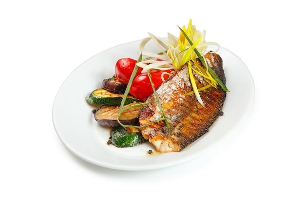 Пряное филе скумбрии на гриле с макро салат из лимона и свежих овощей на тарелку на столе.