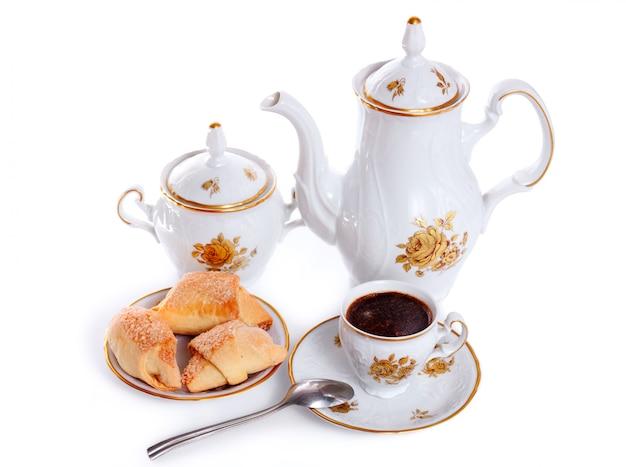 Кофейник с чашкой и блюдцем из пирожных