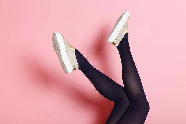 Ноги молодой кавказской женщины в черных колготках и золотых туфлях