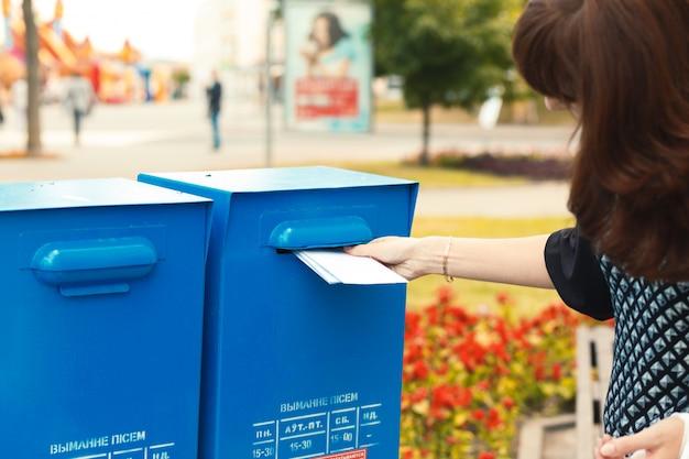 Женщина кладет письма в почтовый ящик