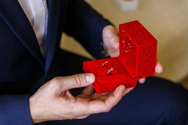青いスーツの男は結婚指輪の小さなギフトボックスを保持します