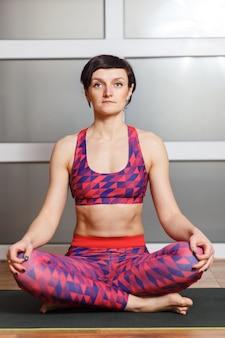 Молодая спортивная женщина делает упражнение сукхасана