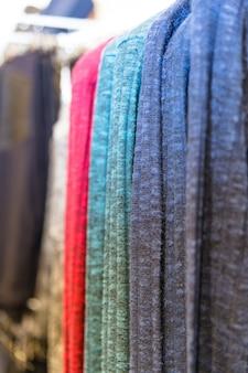 Много цветных джинсовых брюк висит на вешалках в магазине одежды.