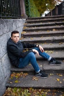 Молодой парень сидит на лестнице.