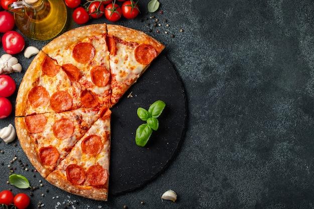 黒いコンクリートの背景においしいペパロニピザ。