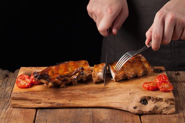 シェフは豚カルビを食べる準備ができているナイフを切る。