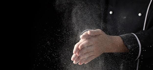 シェフは、黒い背景のバナーに小麦粉を手します。