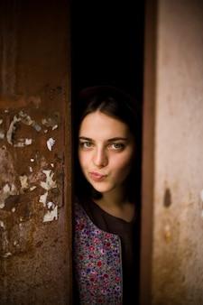 好奇心旺盛な少女がドアの後ろから外を見ています。