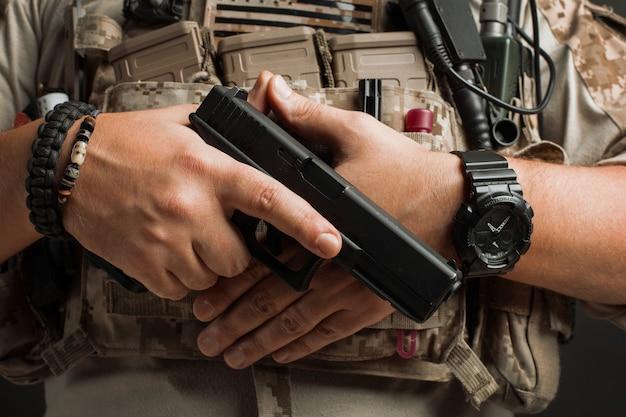 男のクローズアップは彼のホルスターから銃を引きます。