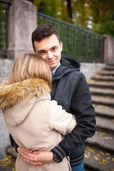 公園で寄り添う女の子を持つ男。