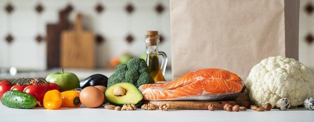 Свежие овощи, фрукты, орехи и стейк из лосося.