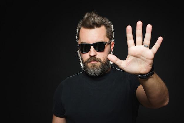 自信を持って男彼の左の手のひらで停止信号を表示します。