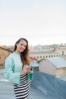 Модель молодой женщины с ретро пленочной камерой.