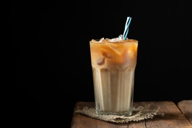 クリーム色の背の高いグラスにアイスコーヒー。