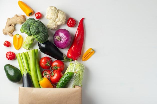 白い背景の上の野菜入り紙袋。