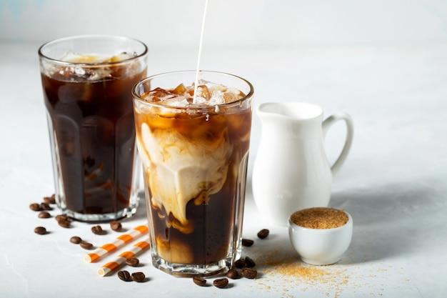背の高いグラスにアイスコーヒーを注いだクリームとコーヒー豆