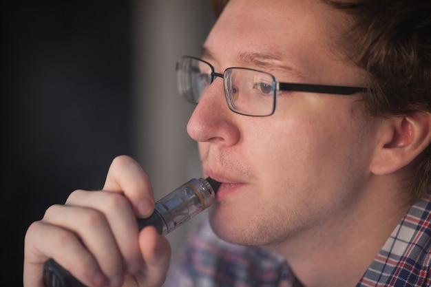 若い男は電子タバコを吸います。