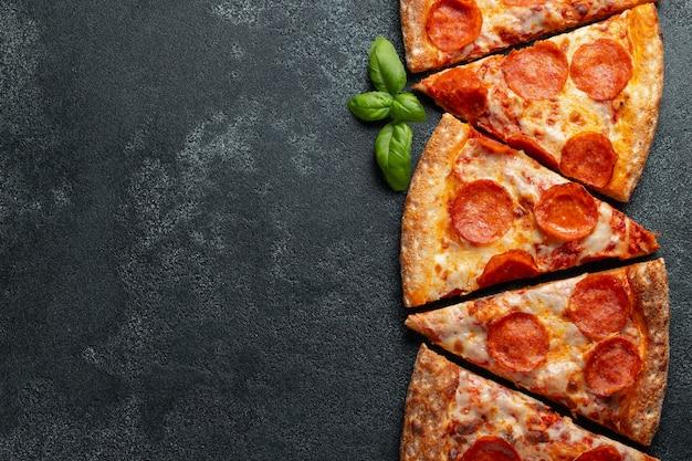 Нарезать ломтиками вкусную свежую пиццу с пепперони
