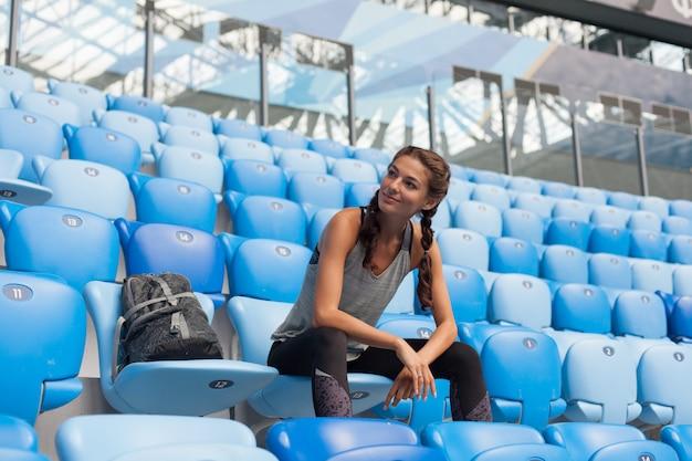 Сексуальная девушка позирует на стадионе.