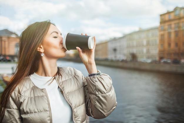 美しい少女はコーヒーを飲みます。