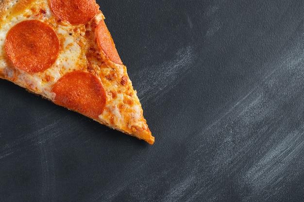 黒のコンクリート背景においしいペパロニのピザ