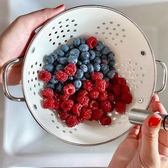 女性の手洗いラズベリーとブルーベリー。