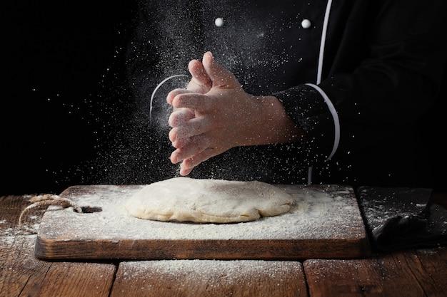 白い小麦粉のスプラッシュと女性シェフの手拍手。